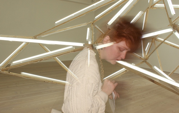 Woman blending with fluorescent lights at Saatchi Gallery